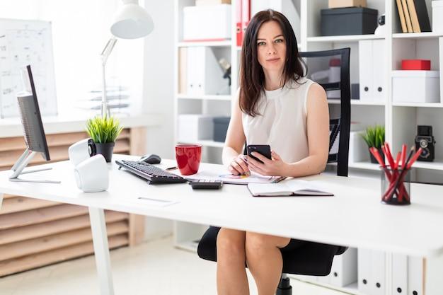 Een jong meisje zit op kantoor op een computer bureau en een telefoon te houden.