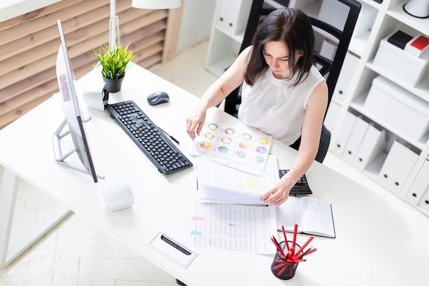 Een jong meisje zit op kantoor op een computer bureau en werken met documenten en een rekenmachine.