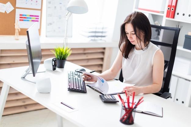 Een jong meisje zit op kantoor op een computer bureau en werken met documenten.