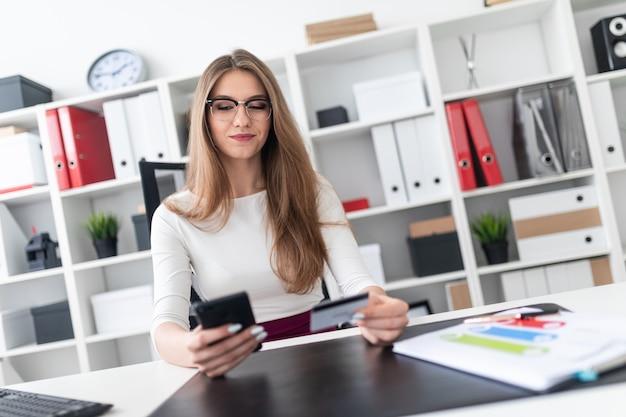 Een jong meisje, zittend aan een tafel en met een telefoon en een creditcard.