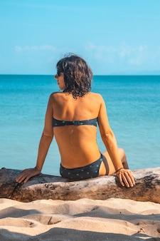 Een jong meisje, zittend in de zon op het strand van punta de sal, tela. honduras