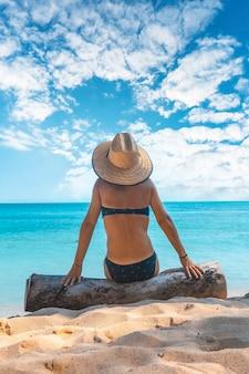 Een jong meisje zittend in de zon op het strand van punta de sal, tela. honduras Premium Foto