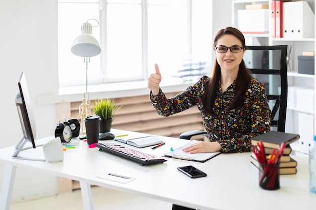 Een jong meisje, zittend in het kantoor op de computer desk en toont het teken goed.