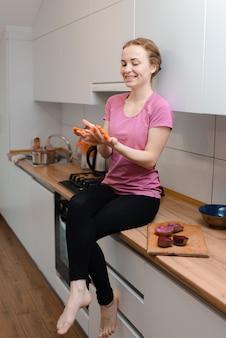 Een jong meisje zittend op de tafel en wortelen in de keuken te houden. thuis koken