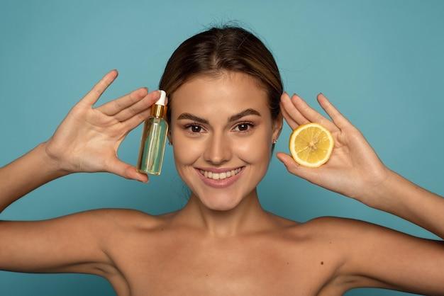 Een jong model houdt een serum met vitamine c en een halve citroen in haar handen op een blauwe achtergrond