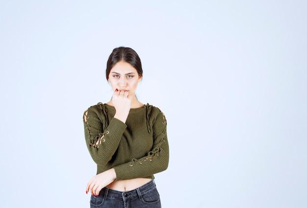 Een jong model in een groene blouse die intens naar de voorkant kijkt