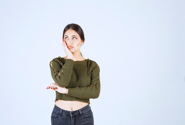 Een jong model in een groene blouse die zich voordeed op een witte muur