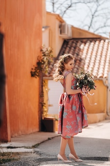 Een jong modelmeisje in een mooie jurk met een boeket bloemen op het platteland in frankrijk. meisje met bloemen in het dorp van de de lenteprovincie.