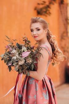 Een jong modelmeisje in een mooie jurk met een boeket bloemen op het platteland in frankrijk