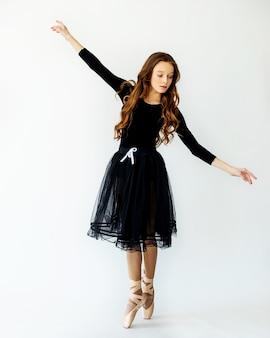 Een jong mooi ballerinameisje staat in beweging op pointe-schoenen in een zwarte zwembroek en rok met een lichte achtergrond.