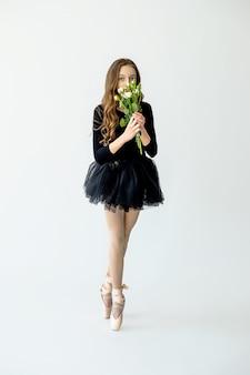 Een jong mooi ballerinameisje staat op pointe-schoenen in een zwart zwempak en een rok met bloemen in haar handen op een lichte achtergrond.