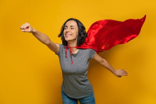 Een jong, mooi meisje dat doet alsof ze een supervrouw is en geniet van vliegen