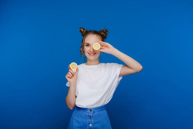Een jong mooi meisje dat op een blauw staat, houdt citroenen in haar handen en bedekt haar ogen ermee.