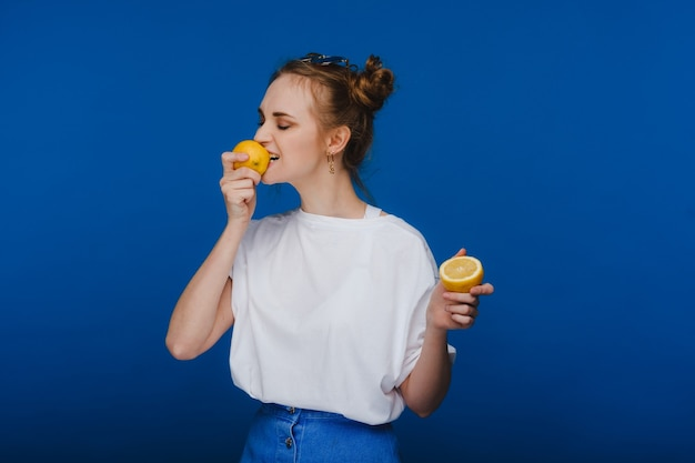 Een jong mooi meisje dat zich op een blauwe achtergrond bevindt die citroenen in haar hand houdt en bijt.