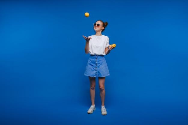 Een jong mooi meisje dat zich op een blauwe achtergrond bevindt die citroenen in haar hand houdt. glimlacht.