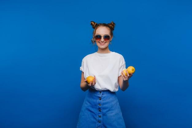 Een jong mooi meisje dat zich op een blauwe holdingscitroenen bevindt in haar hand