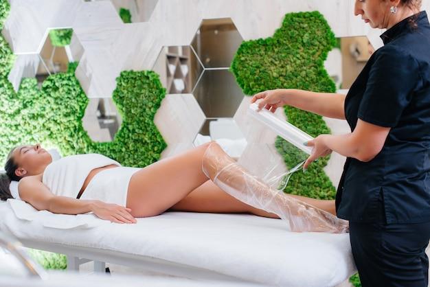 Een jong mooi meisje doet een cosmetologie procedure volledige lichaamspakking in een moderne schoonheidssalon. spa-procedures in een schoonheidssalon.