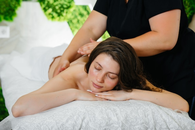 Een jong mooi meisje geniet van een professionele cosmetologische massage in de spa. lichaamsverzorging. schoonheidssalon.