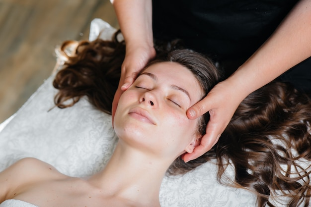 Een jong mooi meisje geniet van een professionele hoofdmassage in de spa. lichaamsverzorging. schoonheidssalon.