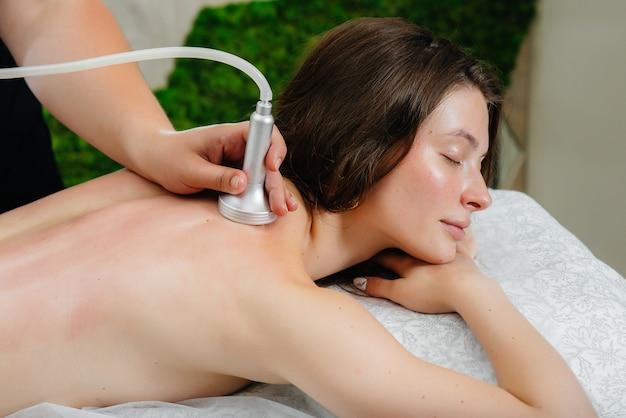 Een jong mooi meisje geniet van een professionele vacuümmassage in de spa. lichaamsverzorging. schoonheidssalon.
