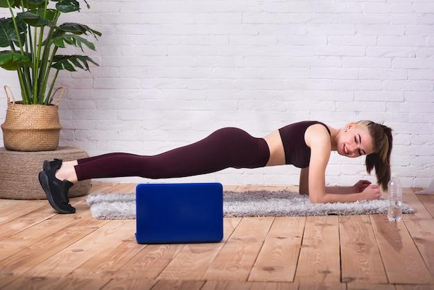 Een jong, mooi meisje houdt zich thuis bezig met fitness. het meisje voert verschillende oefeningen uit met fintes-kauwgom. de atleet wordt getraind via internet