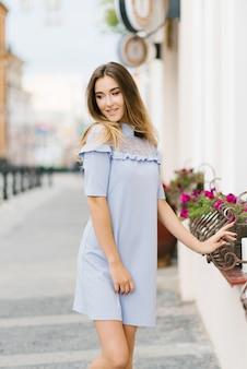 Een jong mooi meisje in een blauwe jurk loopt door de stad
