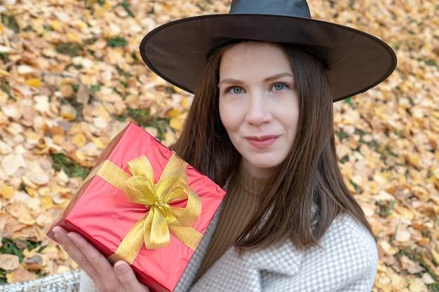 Een jong mooi meisje in een heksenhoed en een stijlvolle jas heeft een rode geschenkdoos
