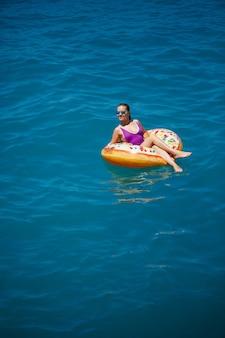 Een jong mooi meisje in een helder zwempak ligt op een grote opblaasbare ring en drijft op de blauwe zee op een heldere zonnige zomerdag