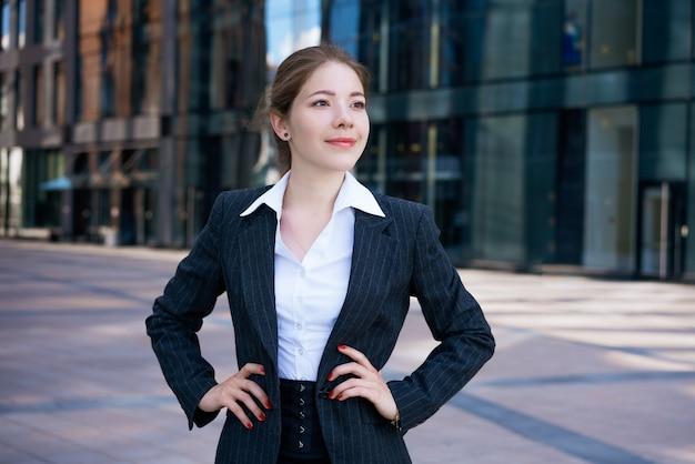 Een jong mooi meisje in een jasje en een wit overhemd vormt tegen de achtergrond van een kantoorgebouw op een zonnige dag
