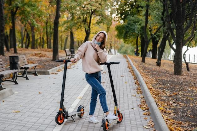 Een jong mooi meisje in een masker rijdt in het park op een elektrische scooter op een warme herfstdag