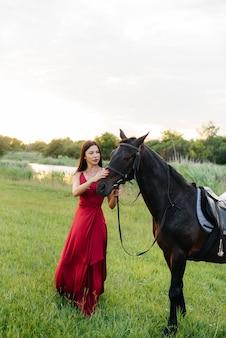Een jong mooi meisje in een rode jurk poseert op een boerderij met een volbloed hengst bij zonsondergang. liefde en zorg voor dieren.