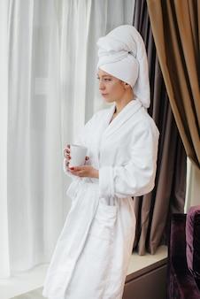 Een jong mooi meisje in een witte jas drinkt koffie in haar hotelkamer