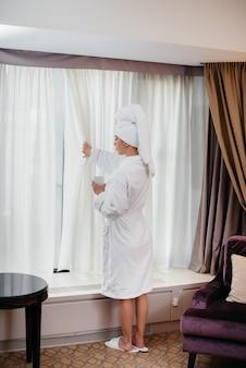 Een jong mooi meisje in een witte jas drinkt koffie in haar hotelkamer.