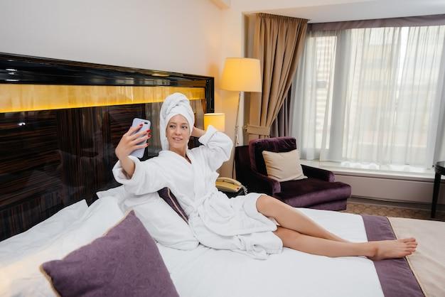 Een jong mooi meisje in een witte jas maakt een selfie op haar telefoon in haar hotelkamer.