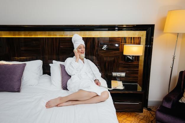 Een jong mooi meisje in een witte jas praat aan de telefoon in haar hotelkamer.