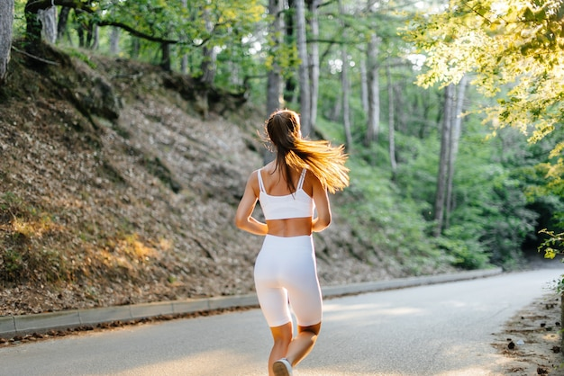 Een jong mooi meisje in witte sportkleding rent met haar rug, op de weg in een dicht bos, tijdens zonsondergang. sporten in de frisse lucht. een gezonde leefstijl.