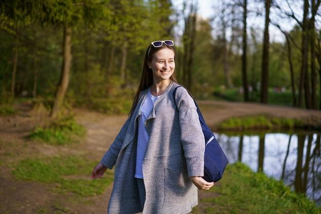 Een jong mooi meisje in zonnebril en met een tas loopt in een bospark in de buurt van het meer op een zonnige dag