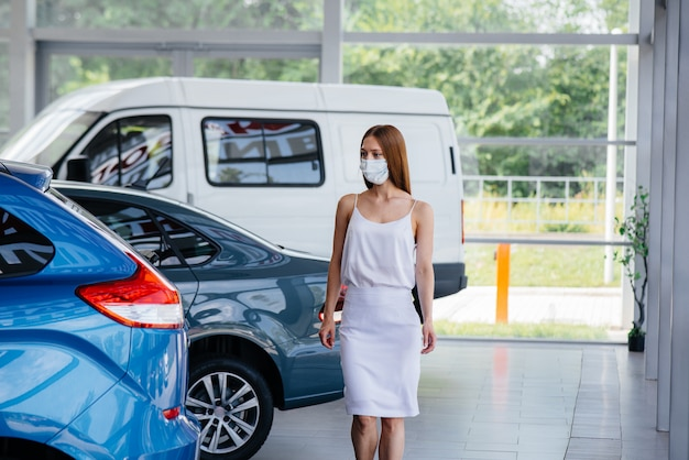 Een jong mooi meisje inspecteert een nieuwe auto bij een autodealer in een masker tijdens de pandemie. de verkoop en aankoop van auto's, in de periode van pandemie.