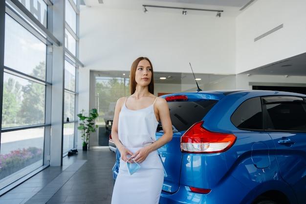 Een jong mooi meisje inspecteert een nieuwe auto in een autodealer. verkoop en aankoop van auto's.