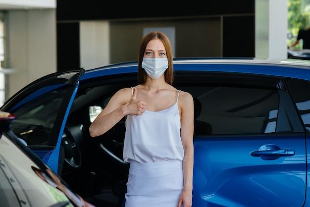 Een jong mooi meisje inspecteert tijdens de pandemie een nieuwe auto bij een autodealer in een masker. de aan- en verkoop van auto's, in de periode van pandemie.