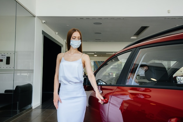 Een jong mooi meisje inspecteert tijdens de pandemie een nieuwe auto bij een autodealer met een masker. de aan- en verkoop van auto's, in de periode van pandemie.