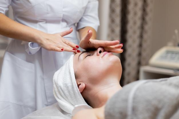 Een jong mooi meisje ligt op de tafel van de schoonheidsspecialiste en krijgt procedures, een lichte gezichtsmassage met olie.