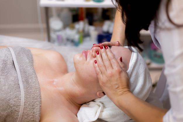 Een jong mooi meisje ligt op de tafel van de schoonheidsspecialiste en krijgt procedures, een lichte gezichtsmassage.