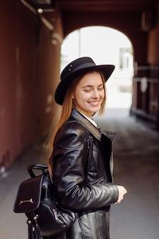 Een jong mooi meisje loopt glimlachend en poseren door de stad