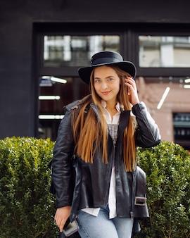 Een jong mooi meisje loopt glimlachend en poseren door de stad Gratis Foto