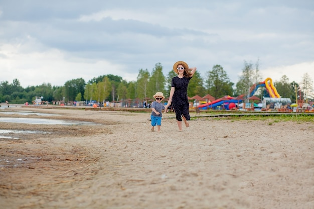Een jong mooi meisje loopt met haar zoon langs een zandstrand in de zee.