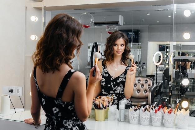 Een jong mooi meisje maakt een mooie avondmake-up voor de spiegel. mode en schoonheid.