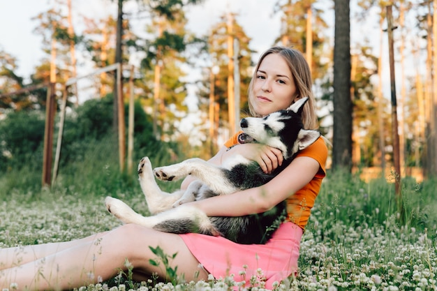 Een jong mooi meisje met blond haar zit op een open plek met haar husky puppy en knuffelt hem.