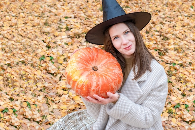 Een jong mooi meisje met een heksenhoed en een stijlvolle jas heeft een grote pompoen in haar handen