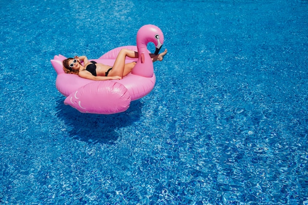 Een jong mooi meisje met een mooi cijfer in een zwart zwempak en zonnebril